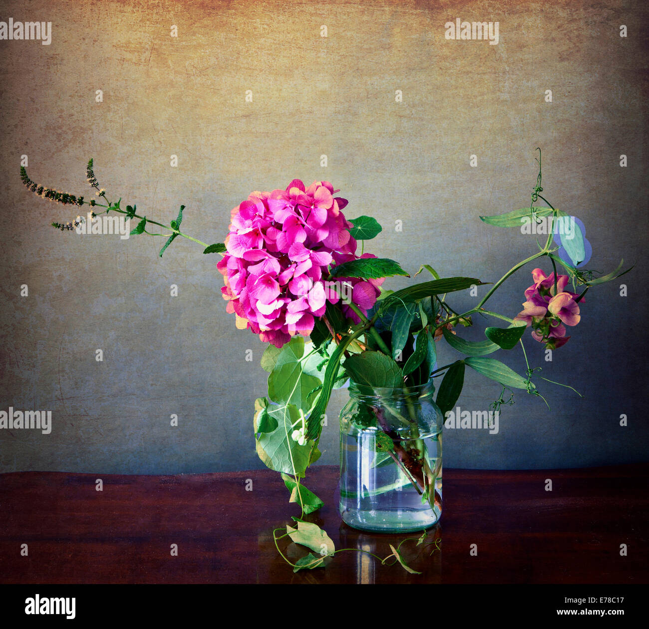 Pink hydrangea and field flowers in a glass with vintage texture and retro Instagram-like effects added - Stock Image