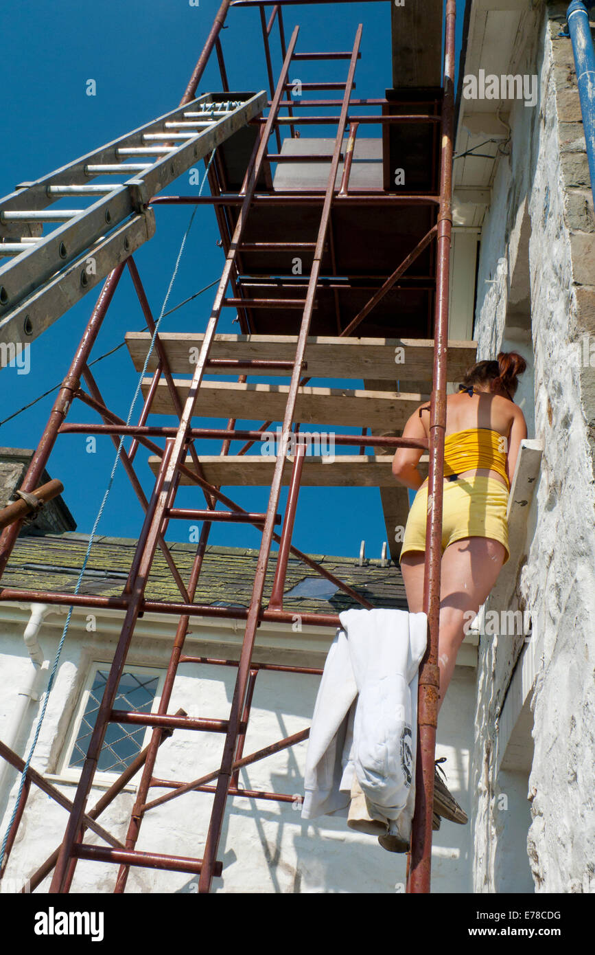 Young woman standing on scaffolding wearing shorts in autumn sunshine preparing a traditional stone farmhouse for - Stock Image
