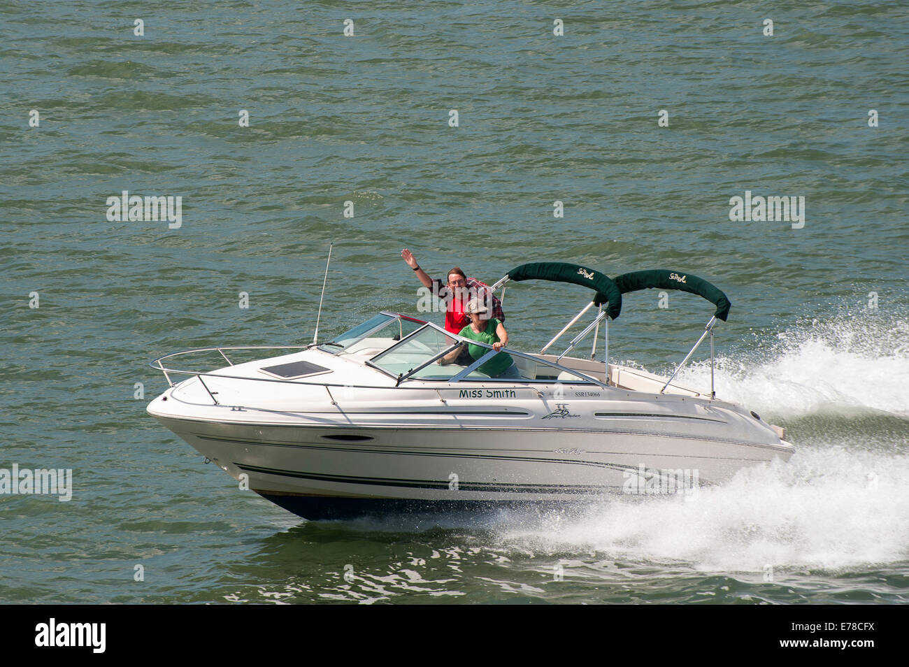 Couple enjoying an afternoon out in a speedboat. Stock Photo