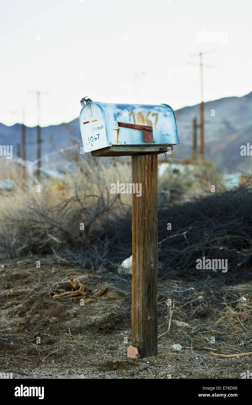 an old blue American mailbox on a wooden post stands rusting, abandoned and alone in front of a rocky skyline on - Stock Image