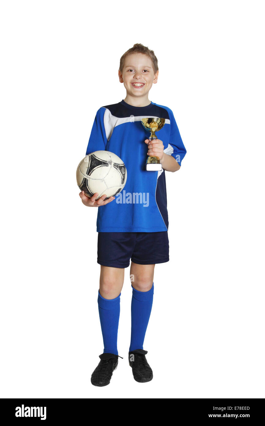 Boy in sports wear with football and winner cup in hands isolated on white background - Stock Image