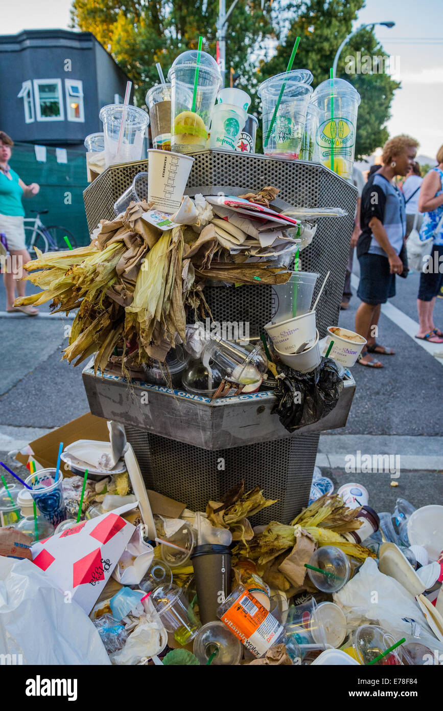 Overflowing litter bin at street event. - Stock Image