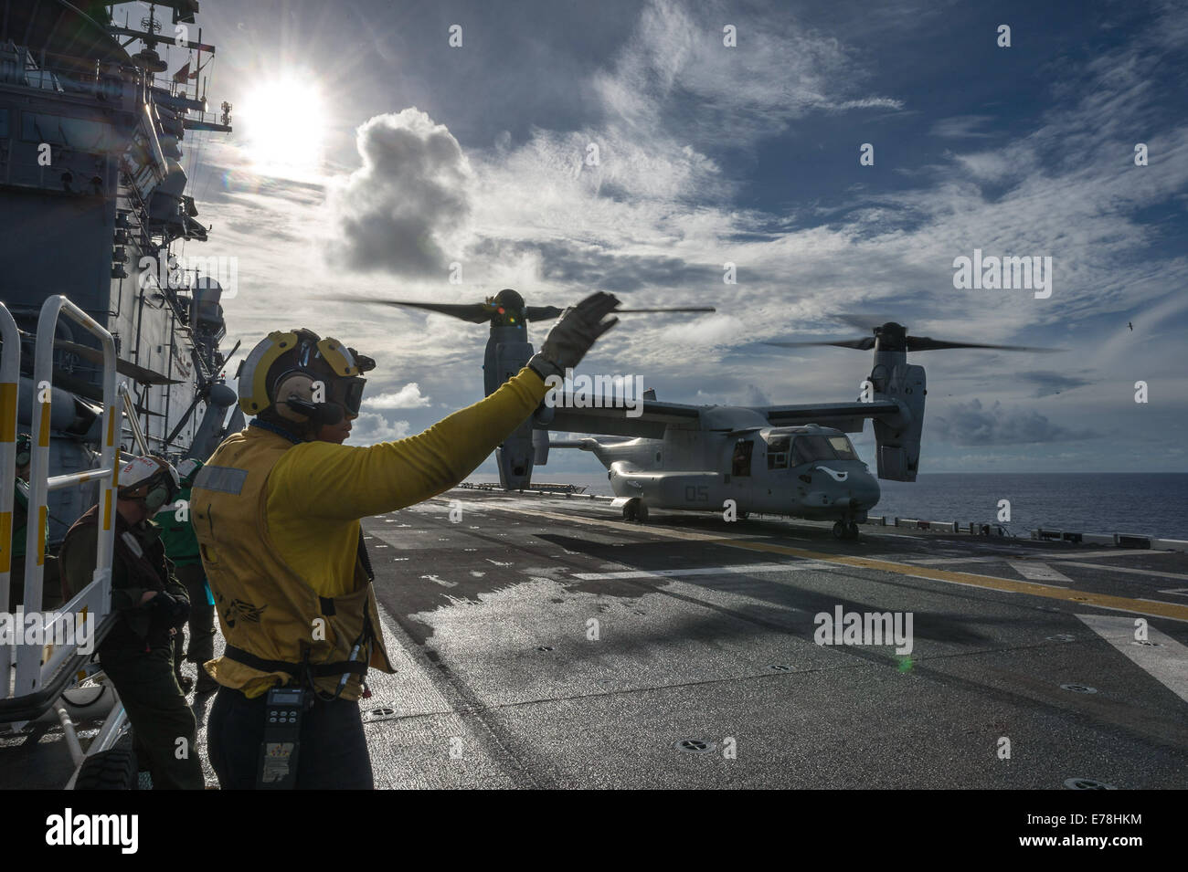 U.S. Navy Airman Juillian R. Sawyer signals to the pilots of a Marine Corps MV-22B Osprey tiltrotor aircraft assigned - Stock Image