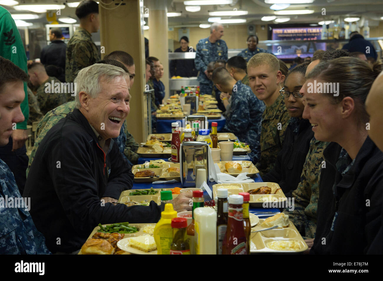 U.S. Secretary of the Navy Ray Mabus, left, has dinner with U.S. Sailors and Marines aboard the amphibious assault Stock Photo
