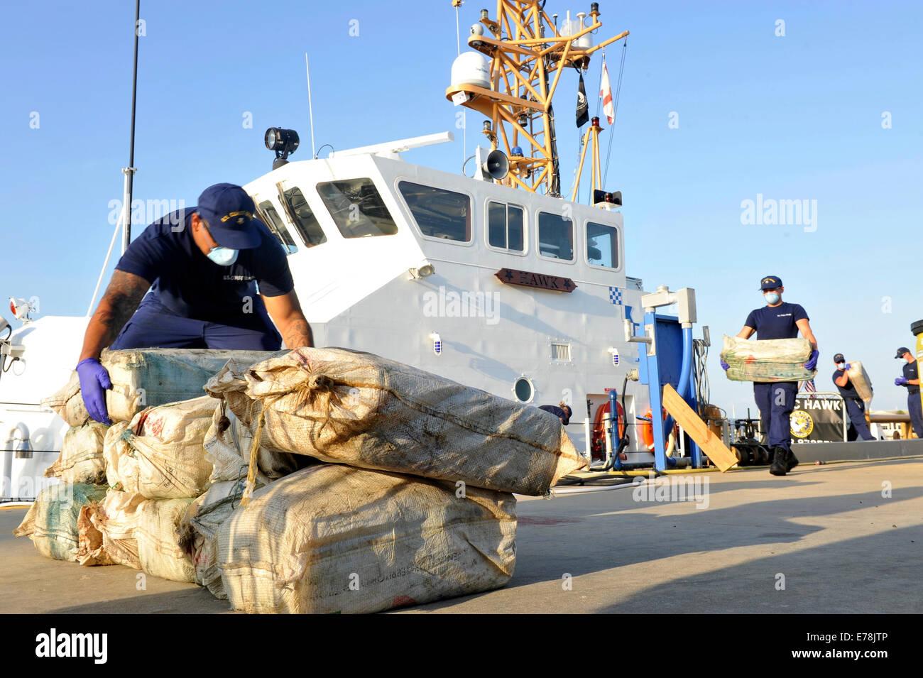 U.S. Coast Guardsmen assigned to the coastal patrol boat USCGC Hawk (WPB 87355) unload 576 kilograms of cocaine, - Stock Image