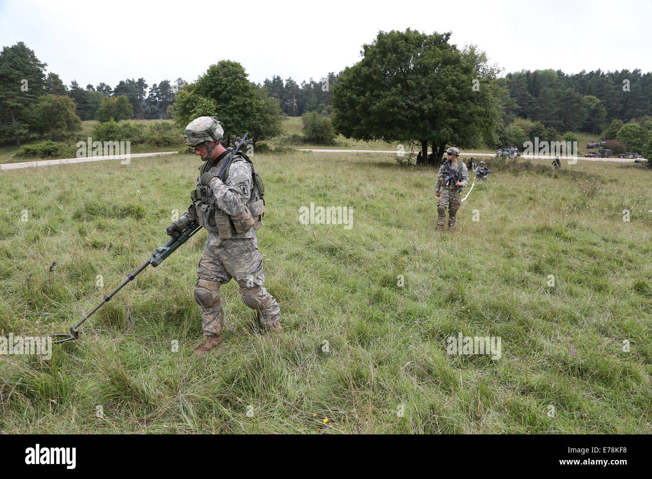 A U.S. Soldier with the 173rd Airborne Brigade Combat Team use a metal detector to safely move through a simulated - Stock Image