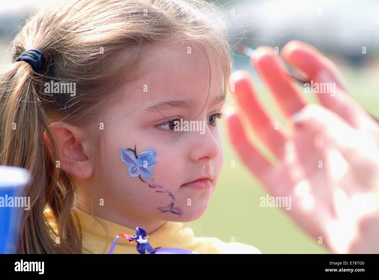 Child undergoing face painting - Stock Image
