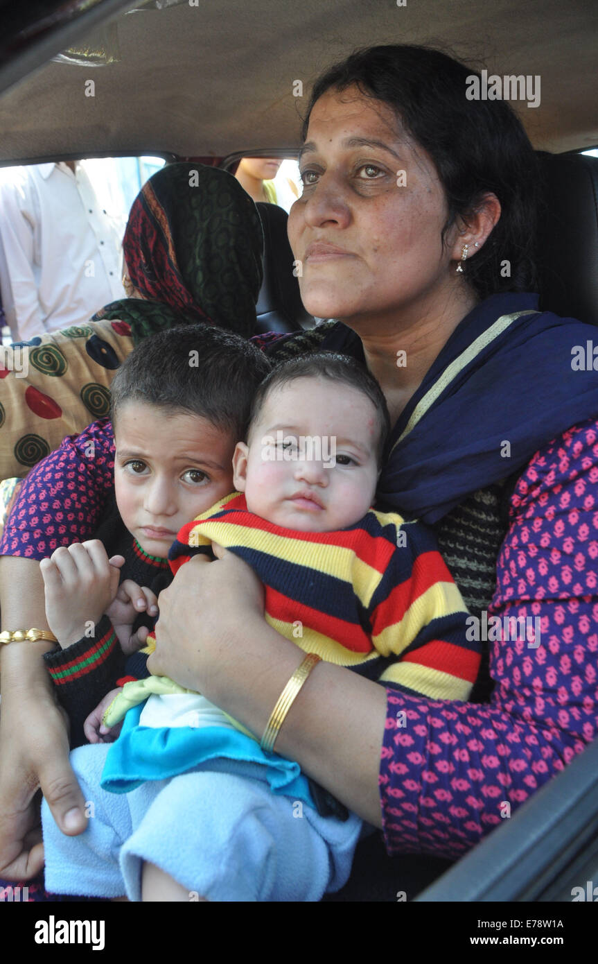 An evacuated Kashmiri resident hugs her children as she arrives outside an Air Force Base in Jammu. Indian Air force - Stock Image