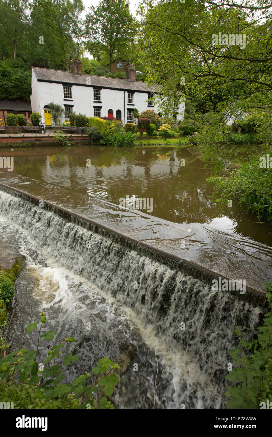 Water running over weir from lake with white painted cottages and colourful gardens on the bank at English village - Stock Image