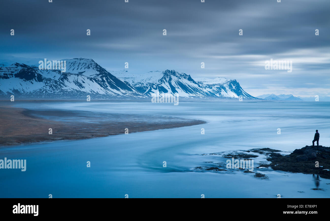 the solitary figure of Wendy on coast at Budir with the mountains of Holsfjall and the Snaefellsnes Peninsula western - Stock Image