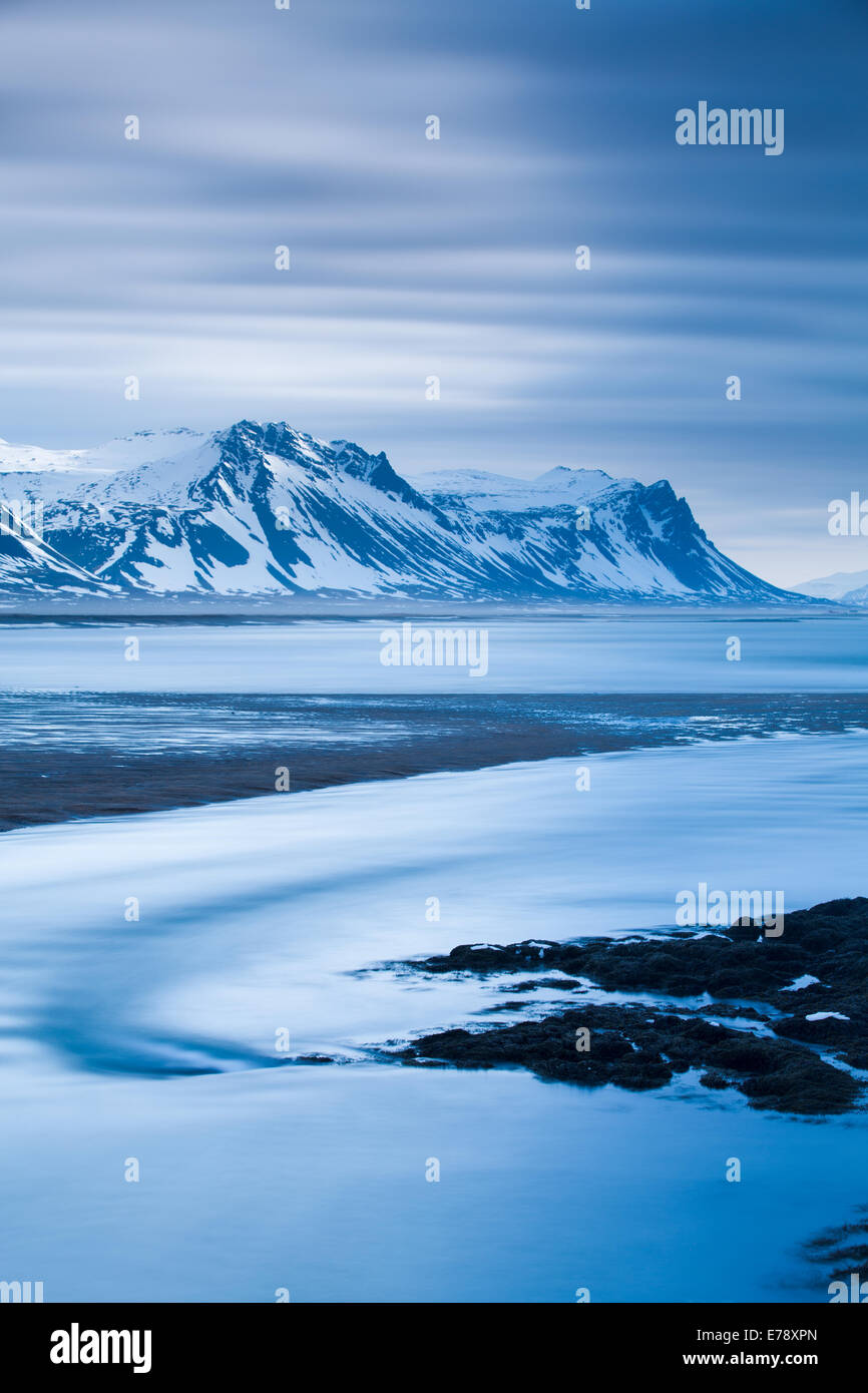 the solitary figure of Wendy on the coast at Budir with the mountains of Holsfjall and Snaefellsnes Peninsula , - Stock Image