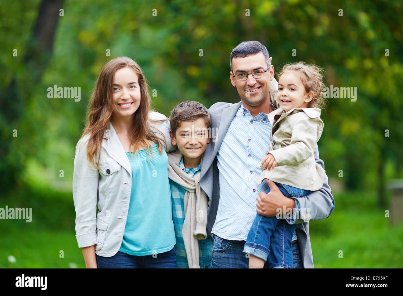 Happy family members looking at camera in natural environment Stock Photo