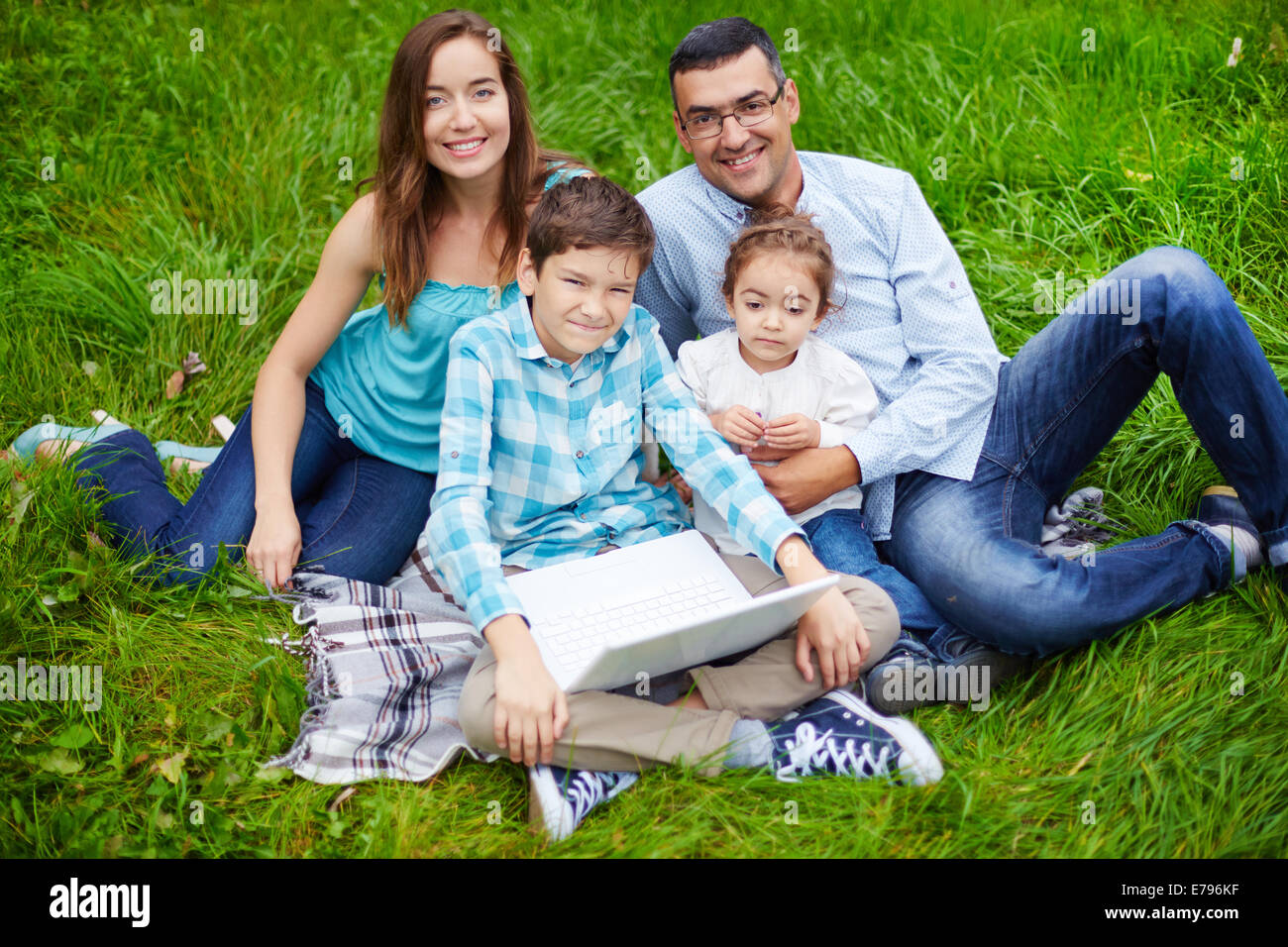 Cute kids and their parents spending time in the park - Stock Image