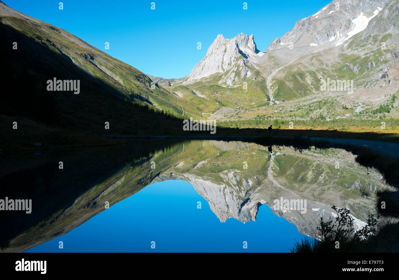 Limestone Pyramids reflected on Combal Lake waters in Val Veny, Italy - Stock Image