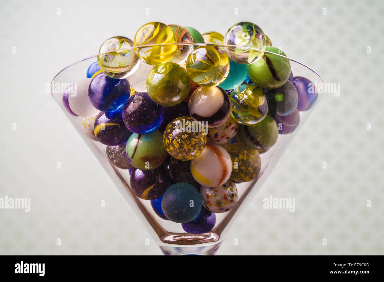 Colorful marbles served in a bowl, ready for playing - Stock Image