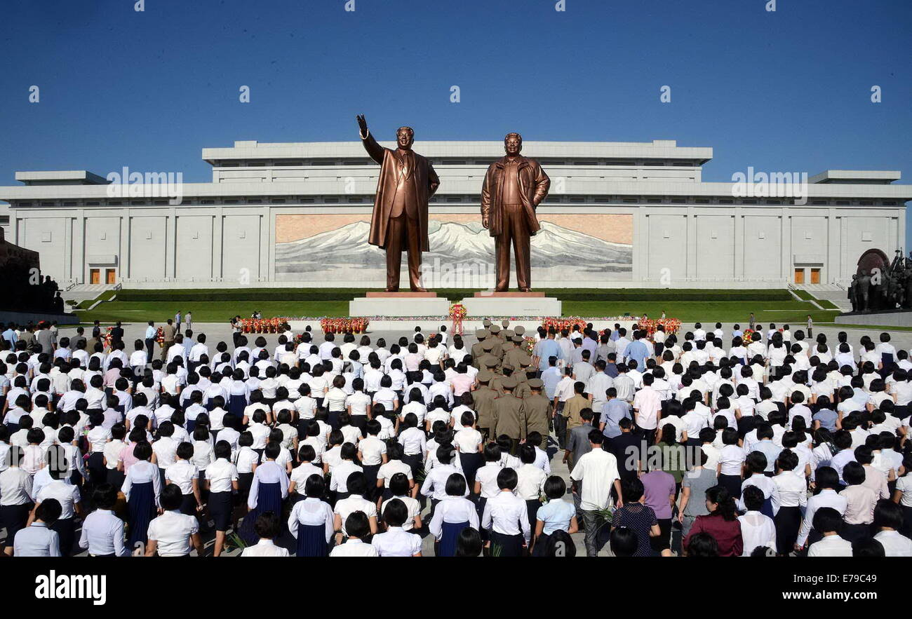 Pyongyang. 9th Sep, 2014. Photo provided by Korean Central News Agency on Sept. 9, 2014 shows people present bouquets - Stock Image