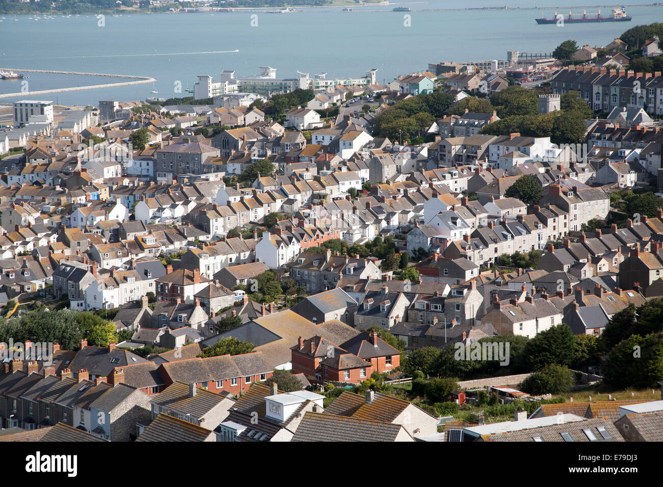 High density housing in Fortuneswell, Isle of Portland, Dorset, England with Weymouth harbour in the background - Stock Image