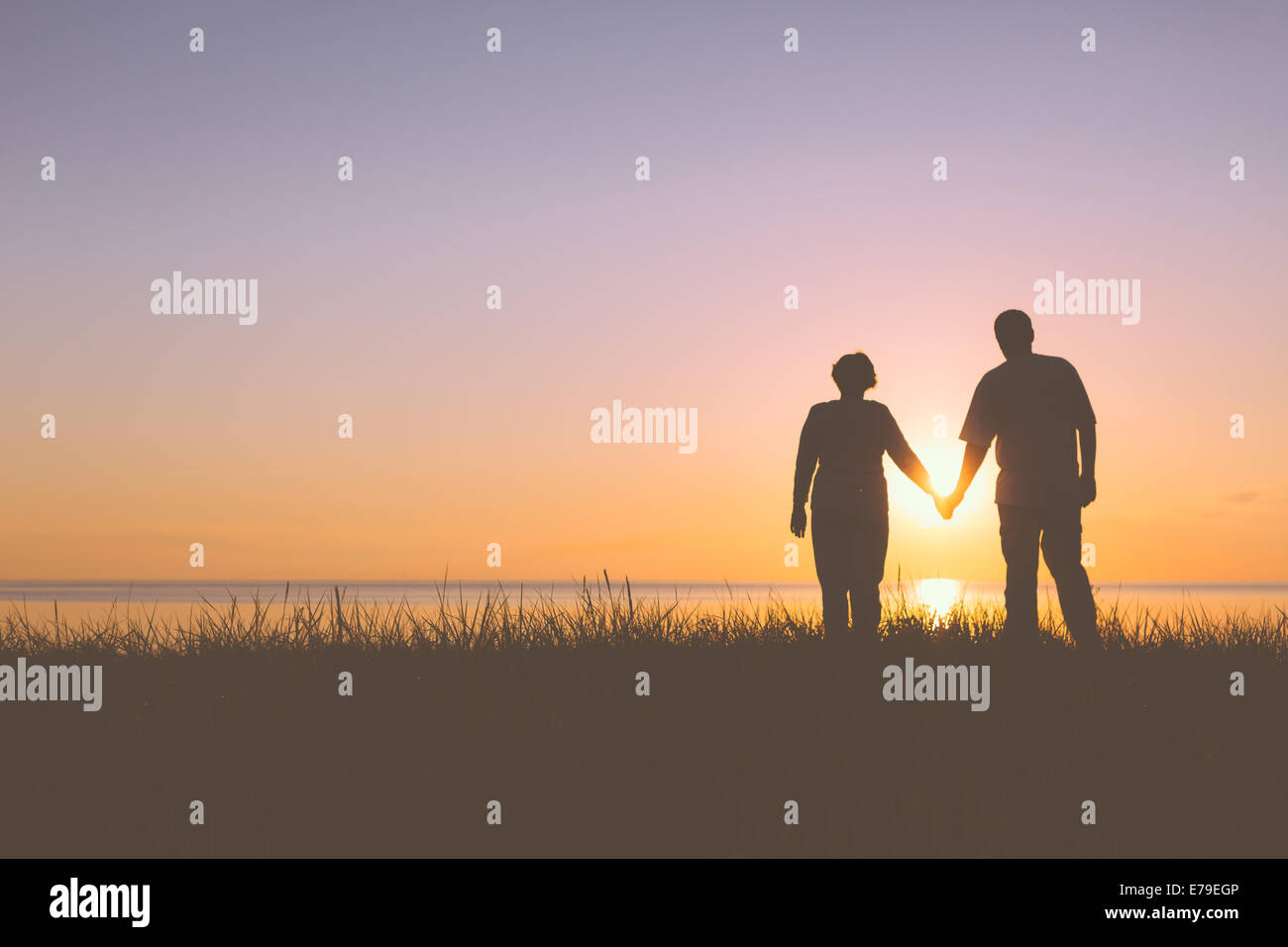 Senior couple holding hands silhouettes - Stock Image