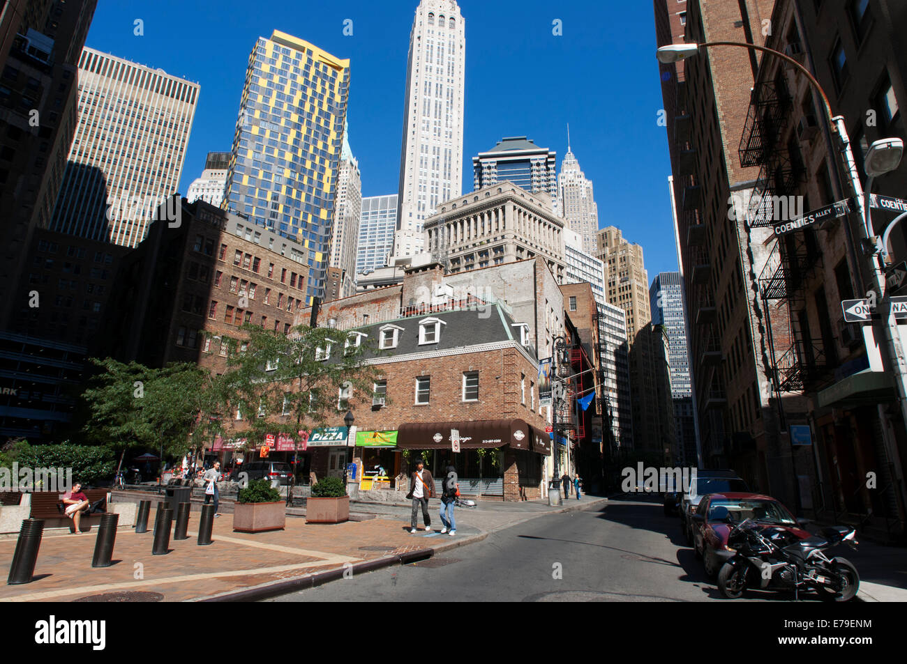 The Financial District of New York City NY. Skyscrapers of the Financial Center. A couple strolls down Coenties - Stock Image
