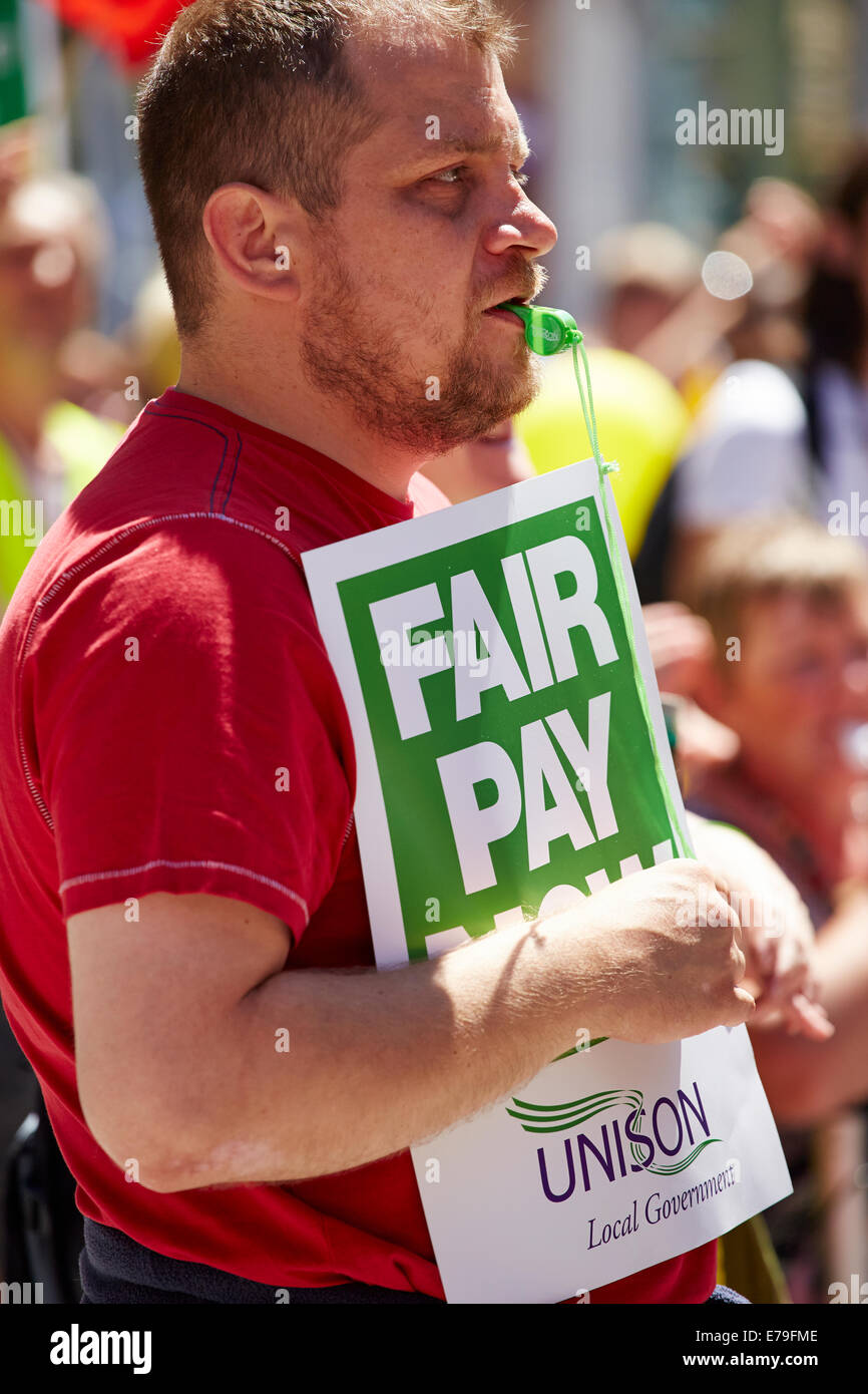 Man holds official Unison fair pay protest board - Stock Image