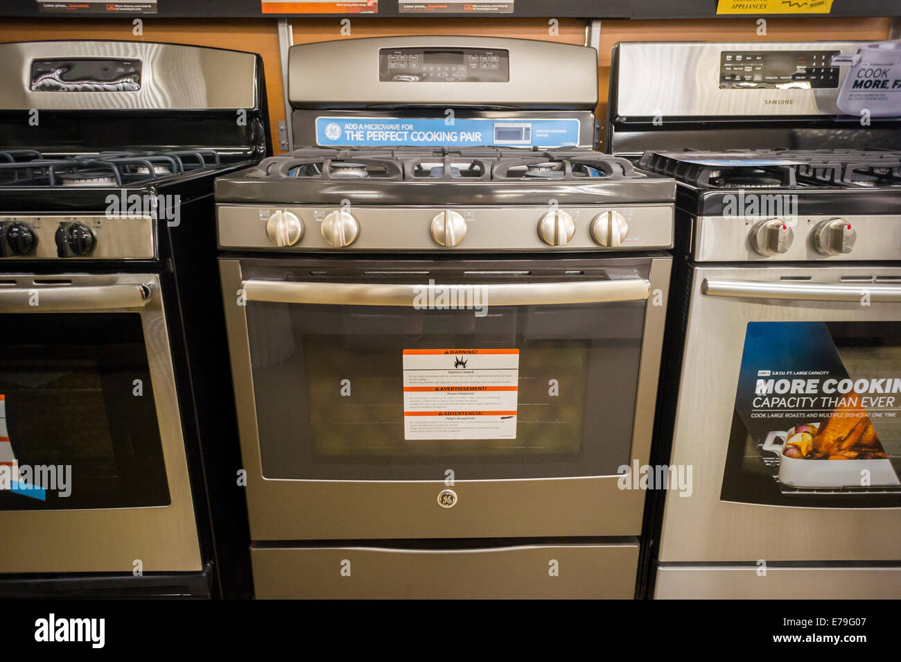 A General Electric gas stove center is seen with other brands in a