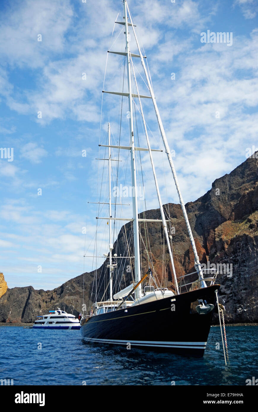 Sailboat by the volcanic cliffs of Isabela Island, Galapagos Islands, Ecuador, South America - Stock Image