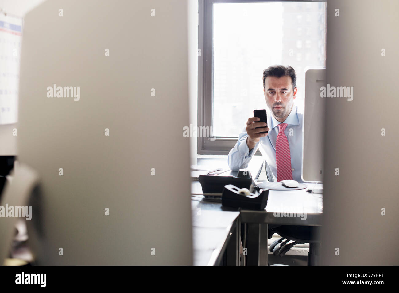 A man checking his smart phone, seated at his office desk. - Stock Image