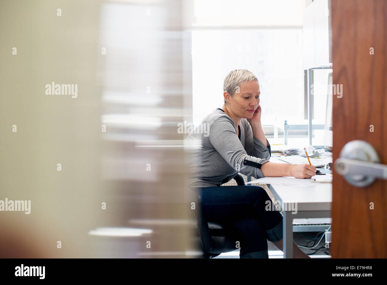 A woman working in an office alone. Focusing on a task, making notes with a pencil. - Stock Image