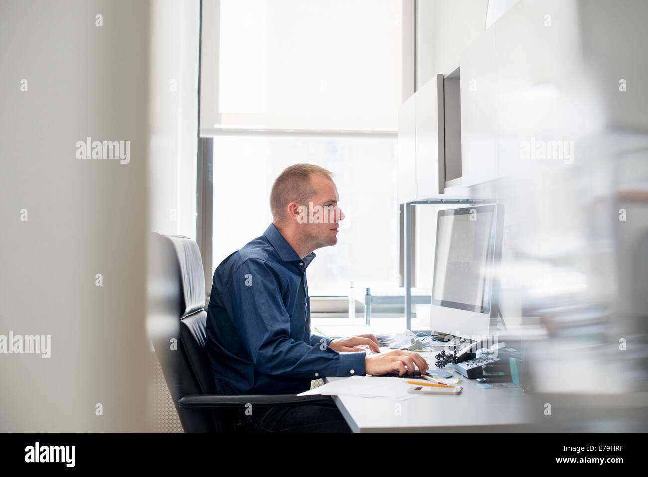 A man working in an office at a desk using a computer mouse. Focusing on a task. Stock Photo