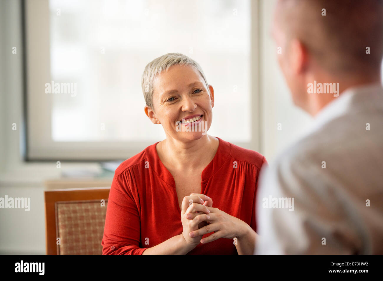 A woman with her hands clasped smiling at a man. - Stock Image