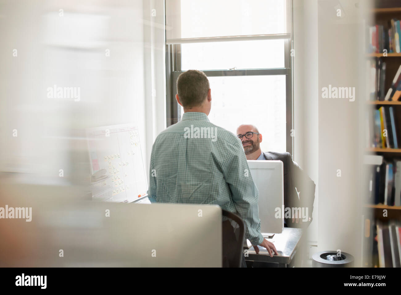 Office life. Two people, businessmen talking to each other over their desks. - Stock Image