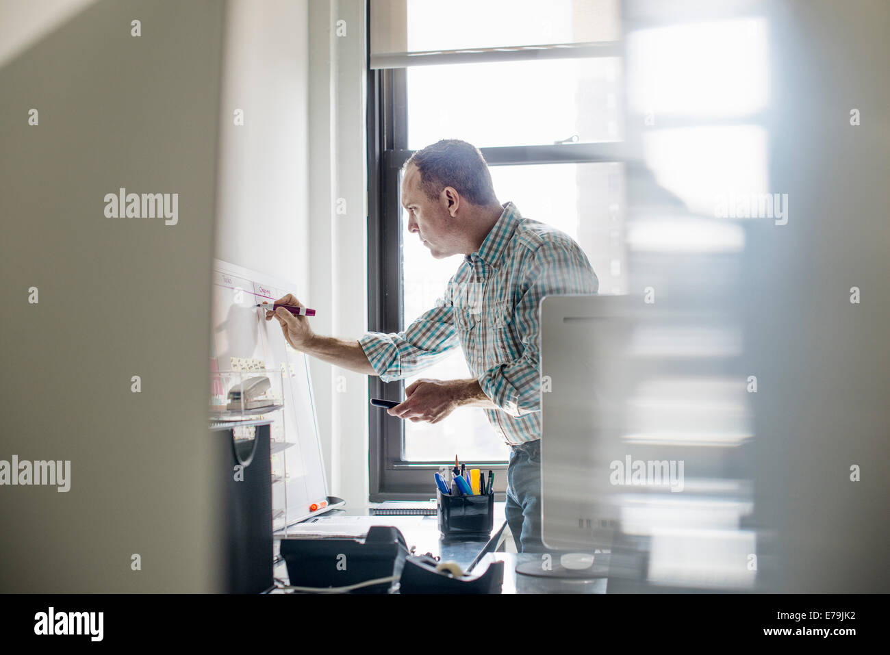 Office life. A man standing up working and making notes on a wall chart. Project management. - Stock Image