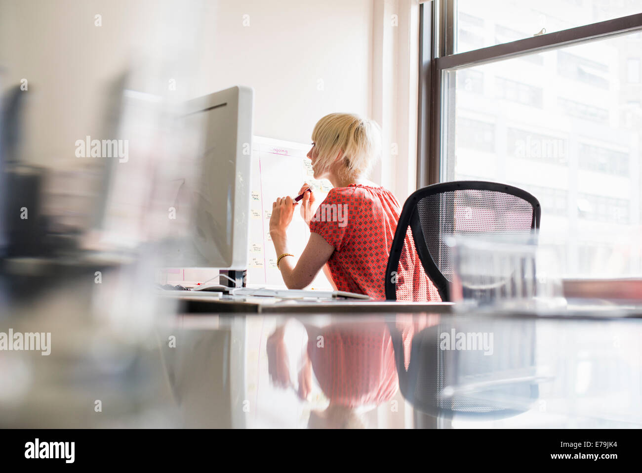 Office life. A young woman working at an office desk. - Stock Image
