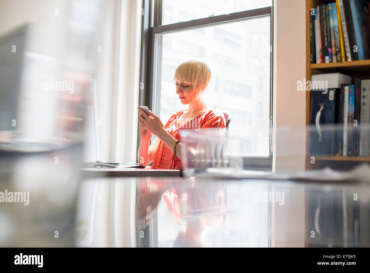Office life. A young woman checking her cell phone. - Stock Image