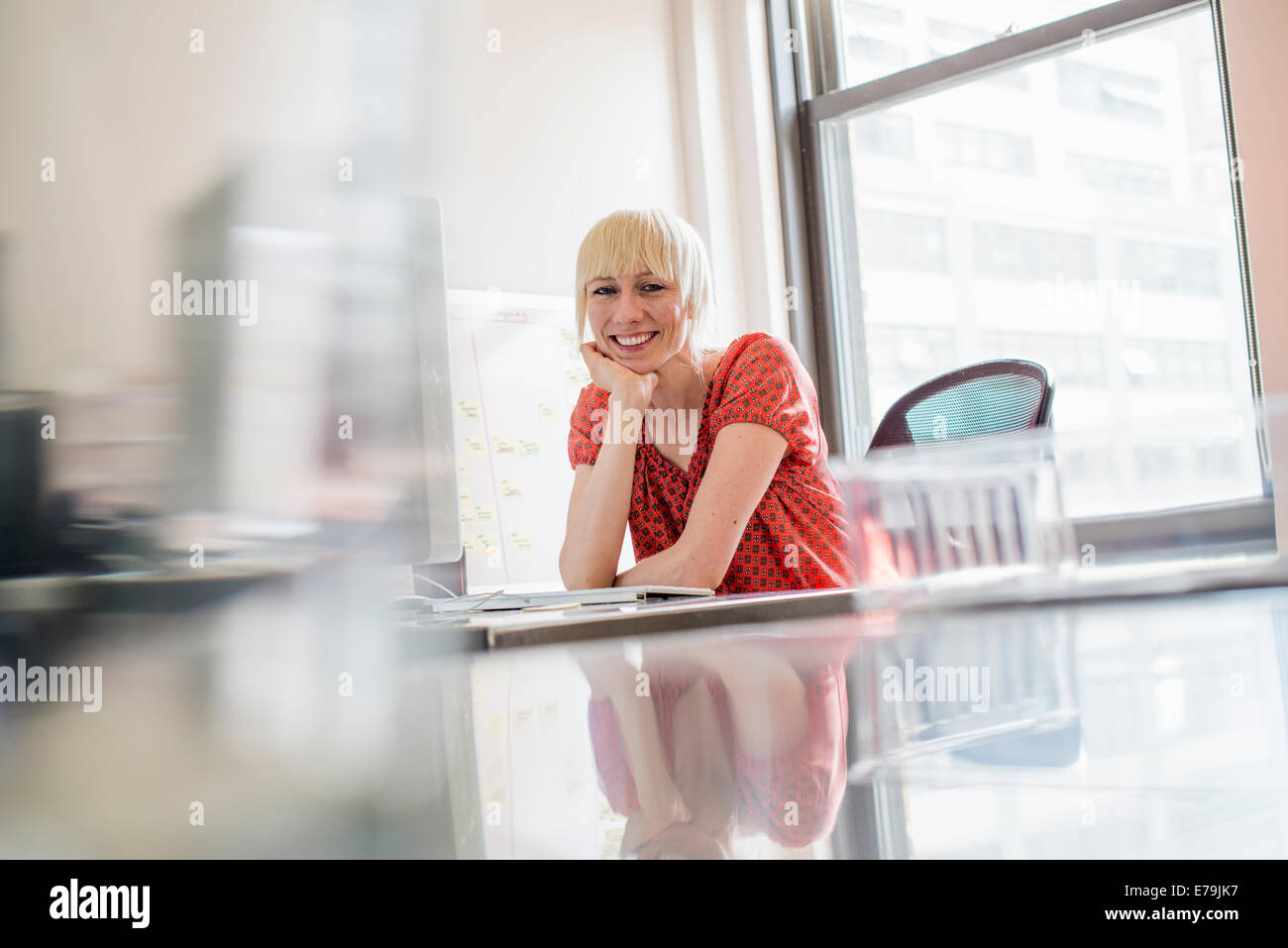 Office life. A young woman sitting at an office desk, her chin resting on her hand, looking at the camera. - Stock Image