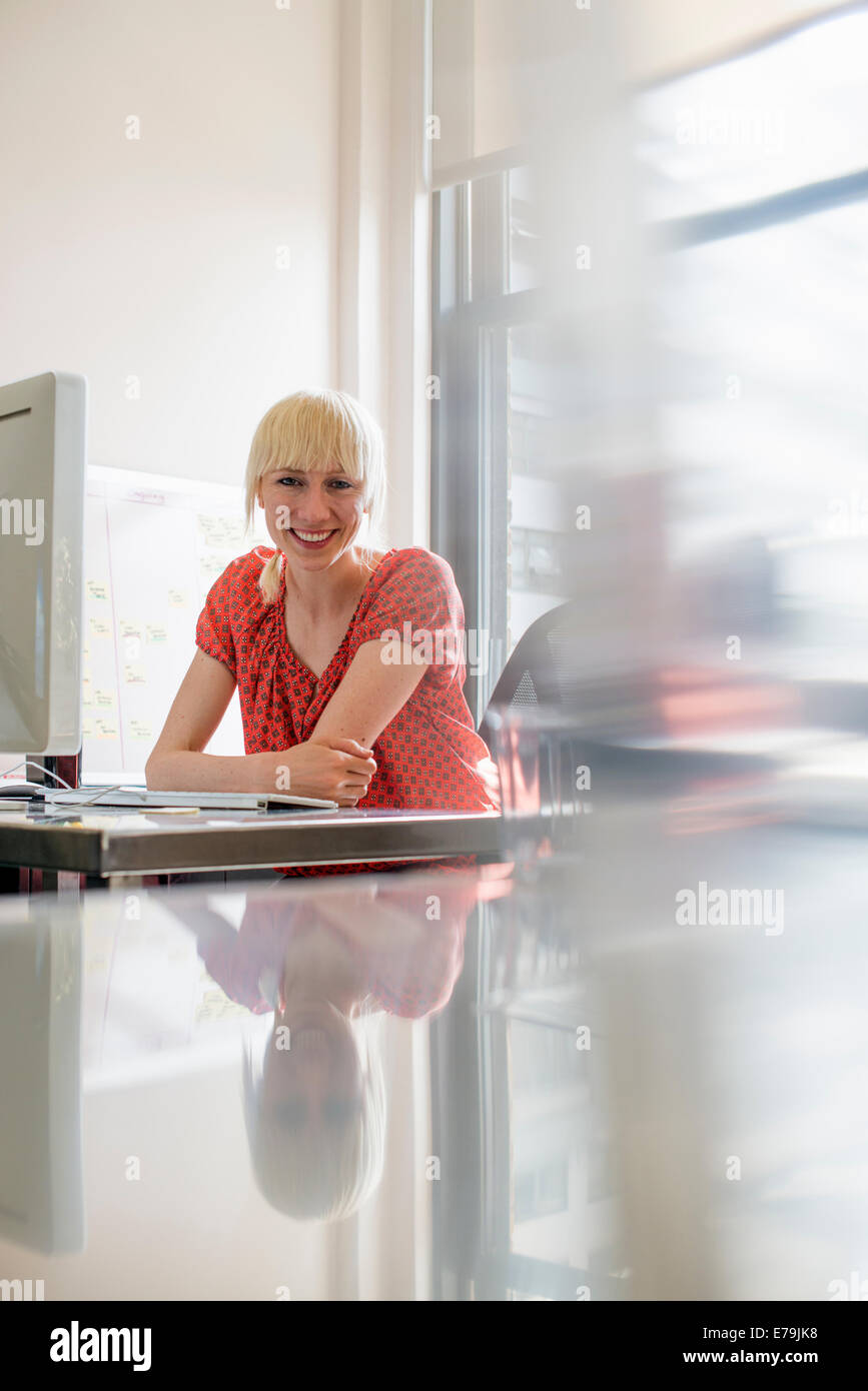 Office life. A young woman sitting at an office desk smiling. - Stock Image
