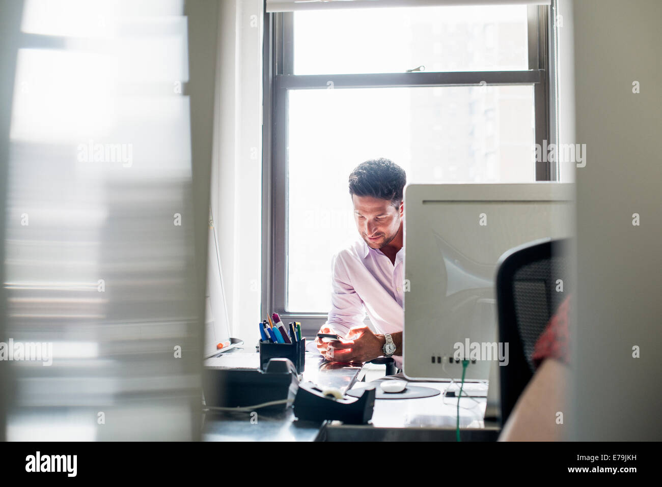 Office life. A man checking his phone in an office. - Stock Image