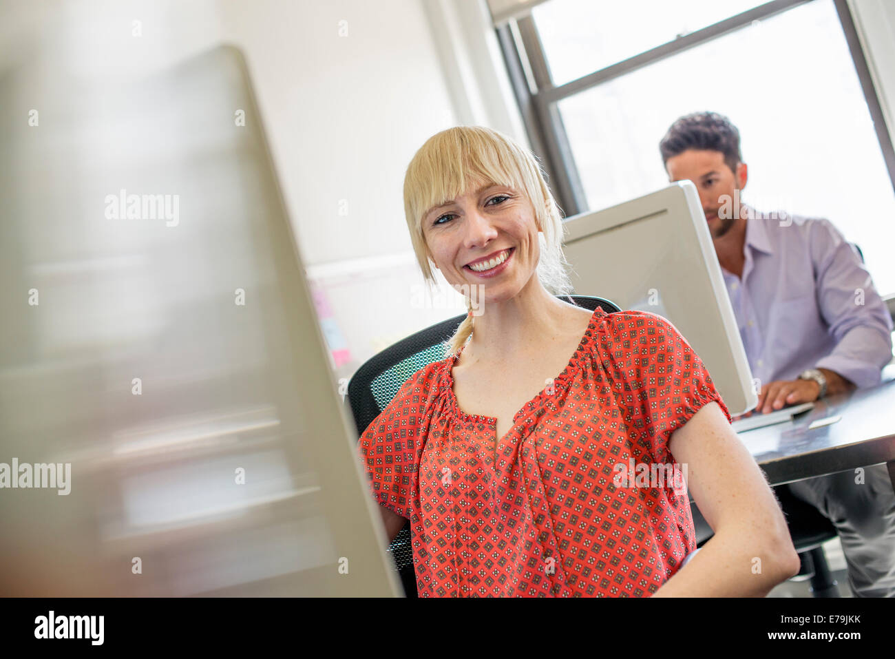 Office life. Two people seated at desks using computers. - Stock Image