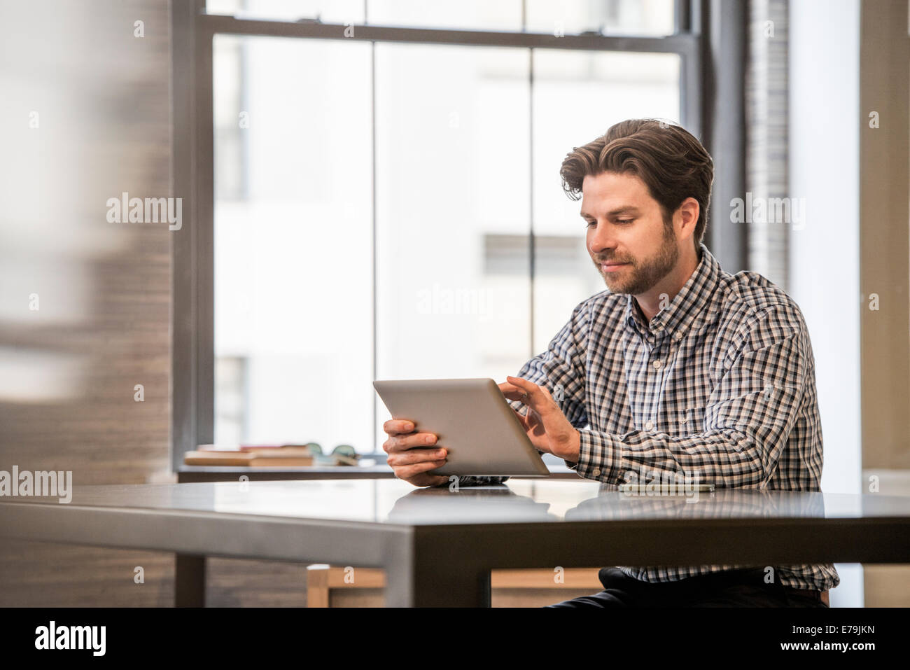 Office life. A man working on a digital tablet at an office desk. - Stock Image