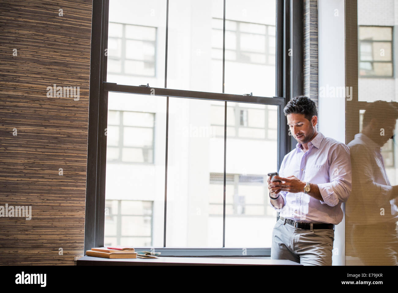 Office life. A man in an office checking his smart phone. - Stock Image