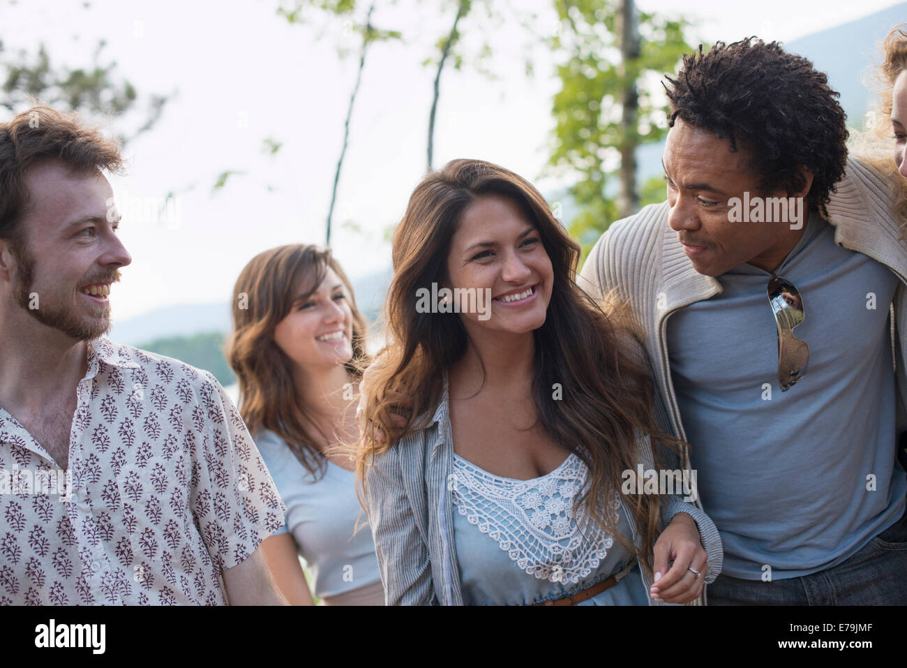 A group of people enjoying a leisurely walk by a lake. - Stock Image