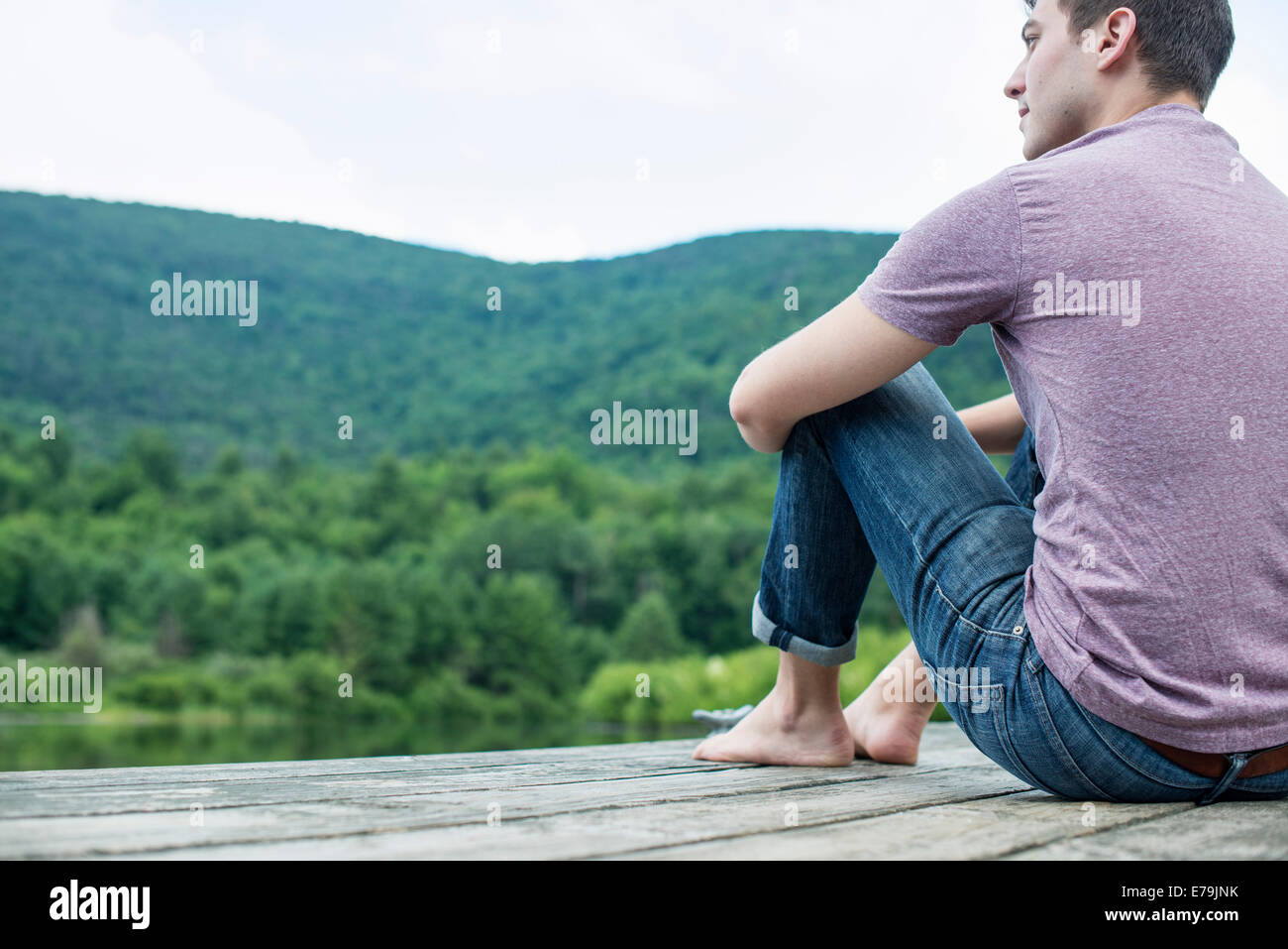 A man sitting on a wooden pier by a lake in summer - Stock Image