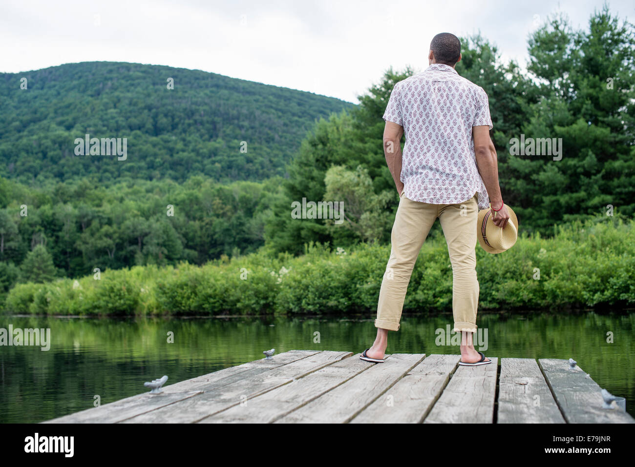 A man standing on a wooden pier overlooking a calm lake. - Stock Image