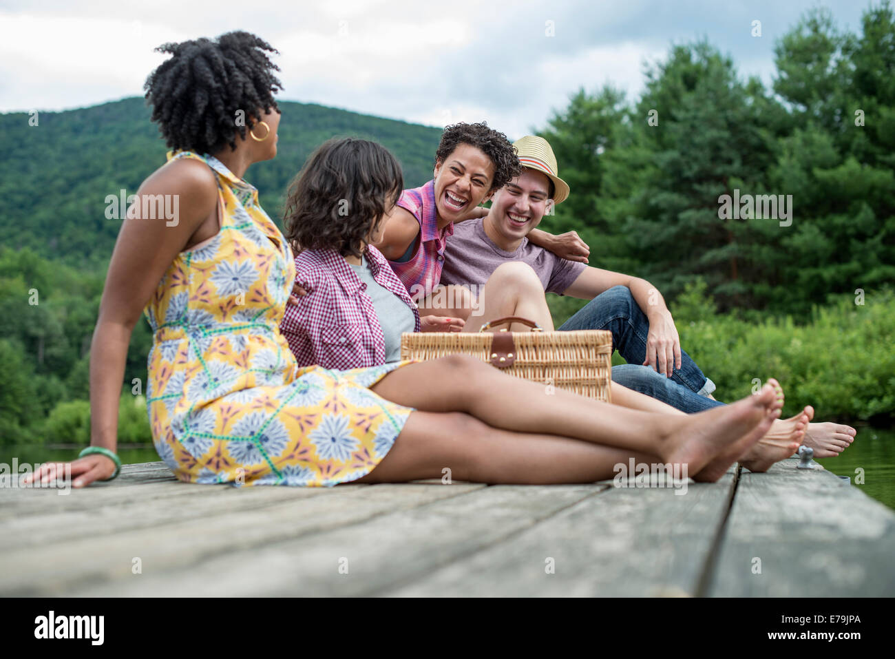 A group of people sitting on a woode pier overlooking a lake. - Stock Image