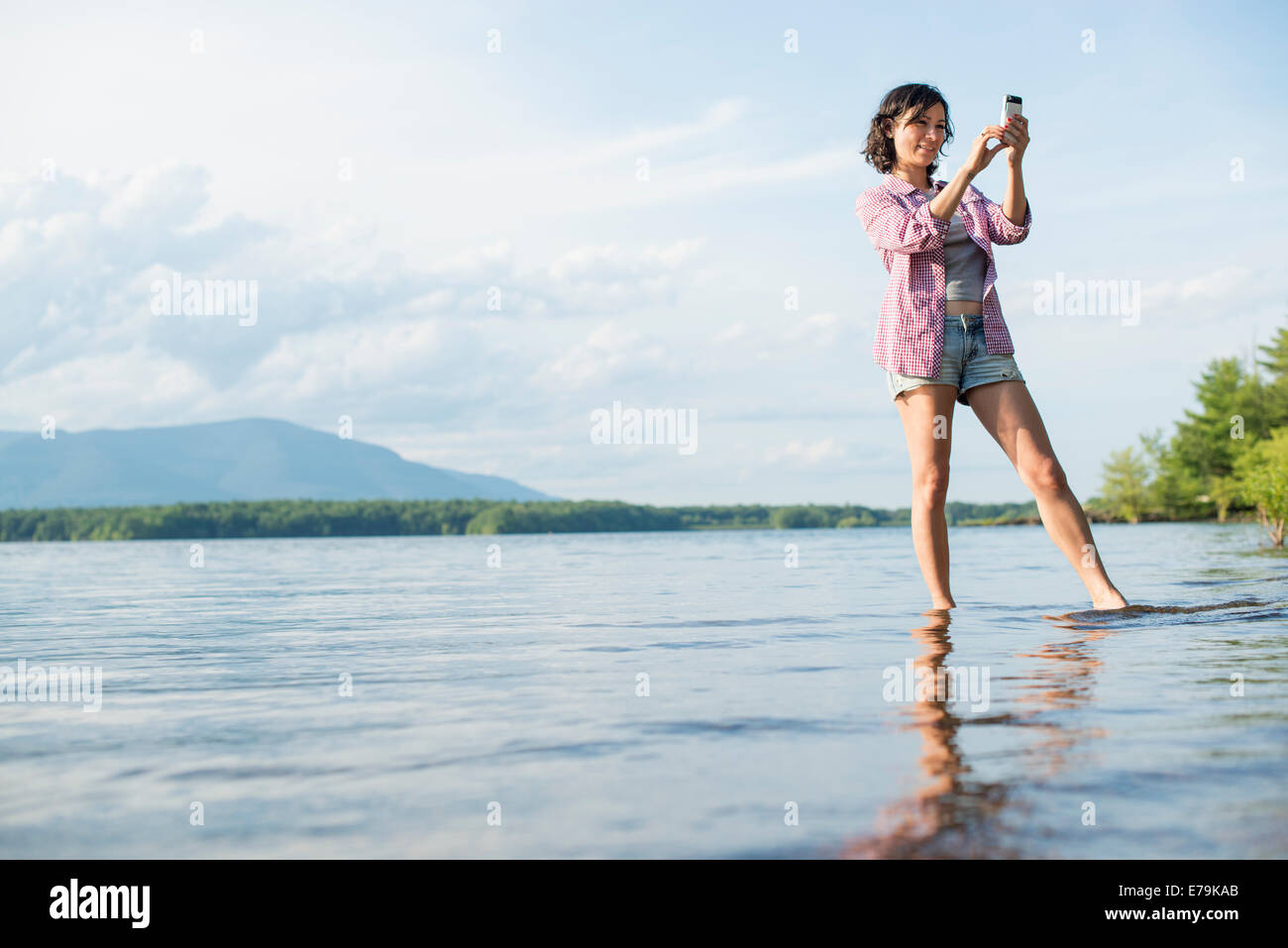 A woman standing in a lake in summer. Taking a photograph. - Stock Image