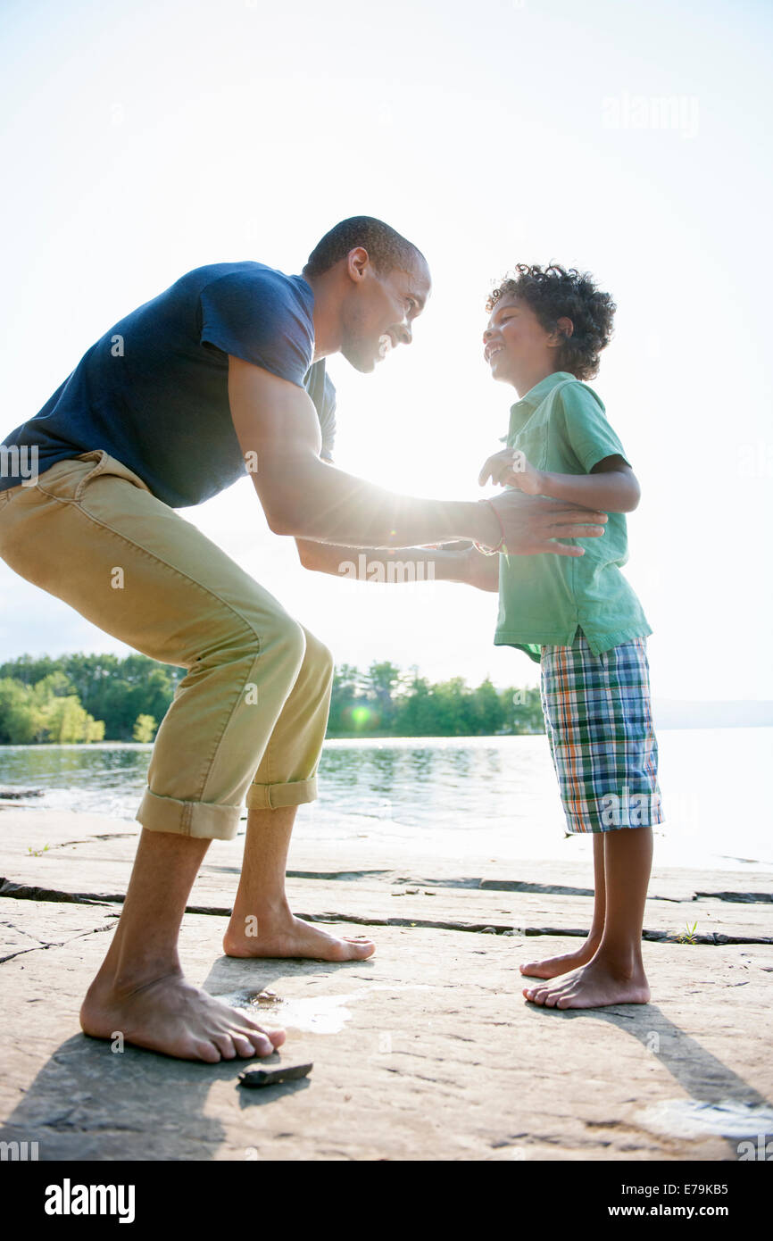 A man lifting a small boy up, playing in the sun by a lake. - Stock Image