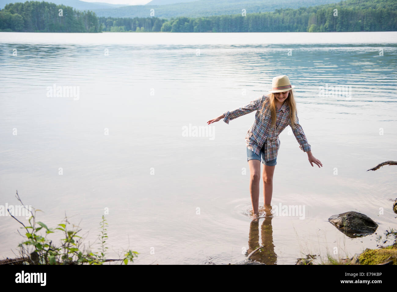 A young girl in a straw hat and shorts paddling in the shallow waters of a lake. - Stock Image