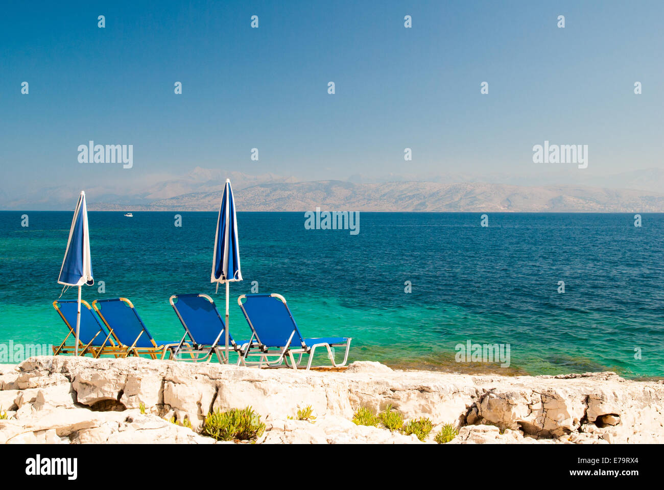 Sunbeds and umbrellas (parasols) on a rocky beach in Corfu Island, Ionian Sea, Greece Stock Photo