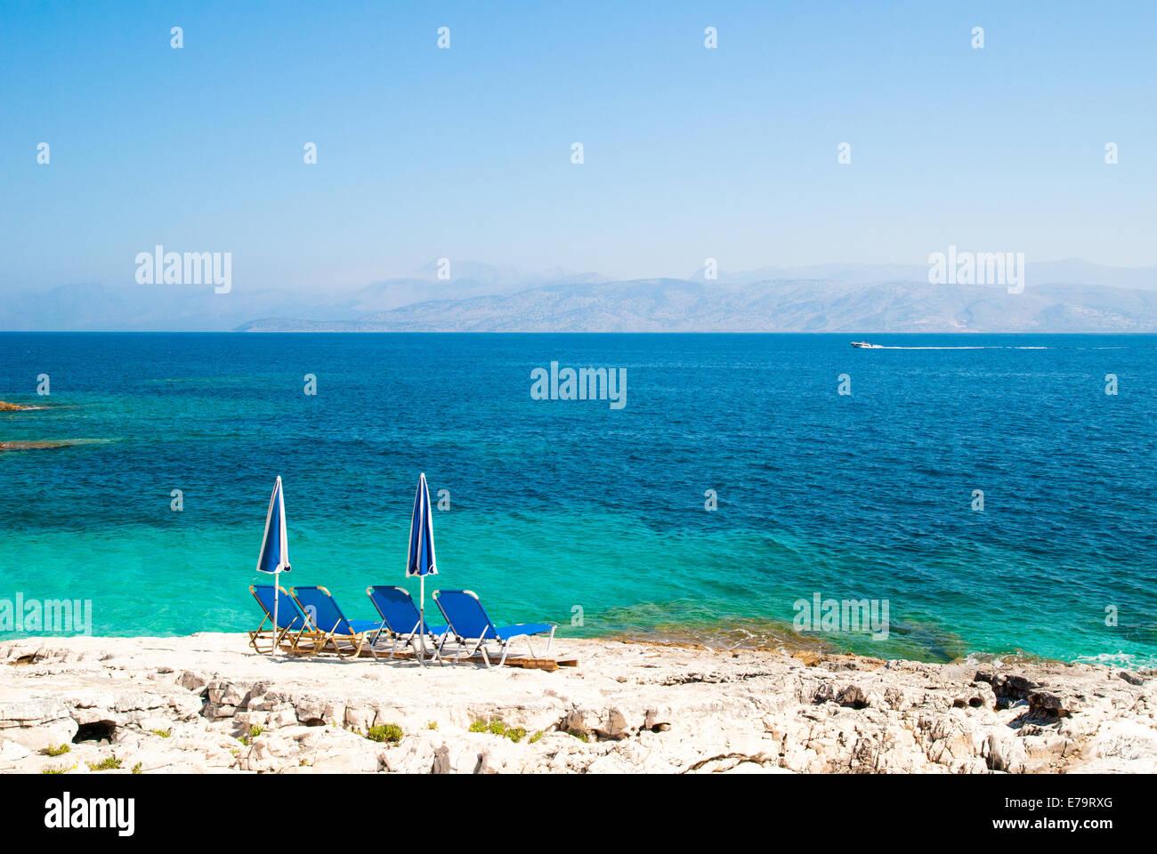 Sunbeds and umbrellas (parasols) on a rocky beach in Corfu Island, Ionian Sea, Greece Stock Photo
