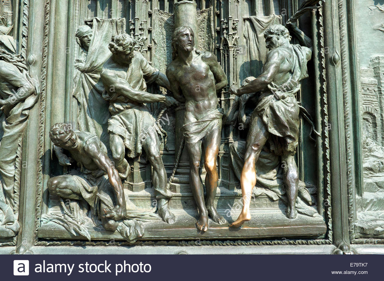 Detail of one of the bronze doors of the Duomo di Milano, showing shiny rubbed parts on the sculpture. Milan, Lombardy, - Stock Image